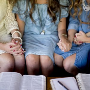 A high angle shot of females holding hands while praying